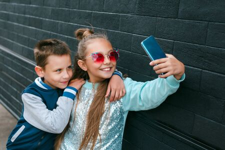 Cute boy and pretty little girl in sunglasses making a selfie using a smart phone and smiling outdoor
