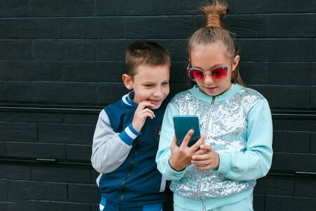 Little boy and girl playing game on mobile phone together