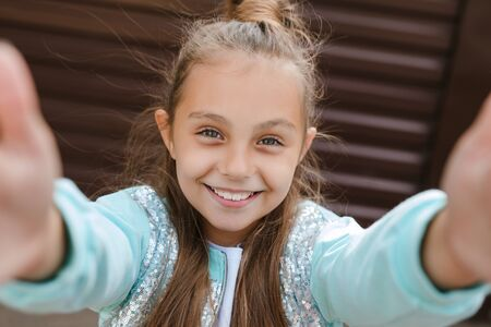 Portrait of a funny little girl taking a selfie in city Reklamní fotografie