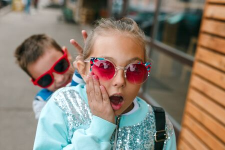 Little stylish kids in sunglasses having fun in city street Reklamní fotografie