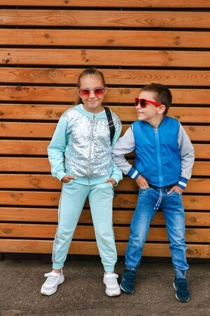 Fashion kids in the city stands on a wooden wall. Trendy boy and girl in sunglasses standing on the street