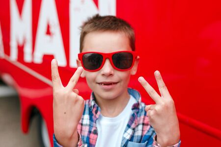 Stylish little boy in red sunglasses shows peace sign outdoor