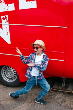 Adorable little boy in trendy clothes and red sunglasses dancing outdoor Reklamní fotografie
