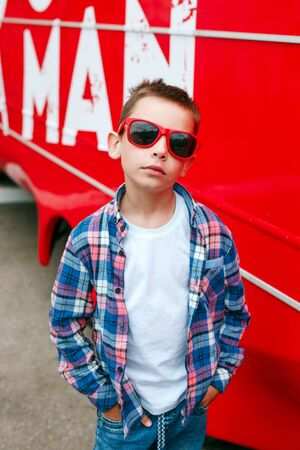 Portrait little boy wearing a checkered shirt and sunglasses in city over red background