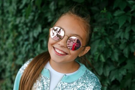 Stylish little girl child wearing a summer or autumn clothes, sunglasses outdoor