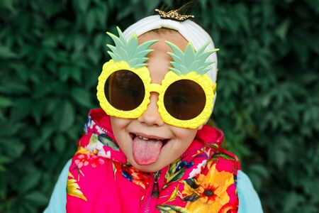 funny little girl with glasses pineapple shows tongue