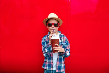 Little boy in sunglasses and hat is drinking milk cocktail over red sicy background Reklamní fotografie