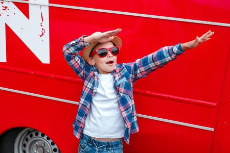 little boy wearing a checkered shirt and sunglasses standing in dab dance pose in city