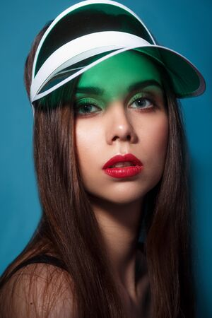Beautiful woman with make-up and red lips in green gel cap visor on the blue background Reklamní fotografie
