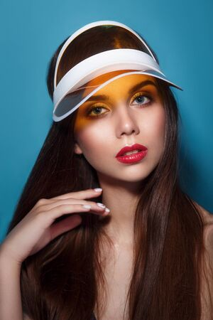 Close-up summer portrait of a beautiful young woman with red lips wearing yellow sun visor. Reklamní fotografie