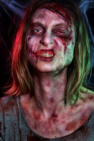 Close-up portrait of horrible zombie woman with wounds. Horror. Halloween make-up and costume 스톡 콘텐츠