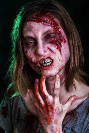 Close-up portrait of horrible zombie woman with wounds. Horror. Halloween poster. The shouting female zombie 스톡 콘텐츠