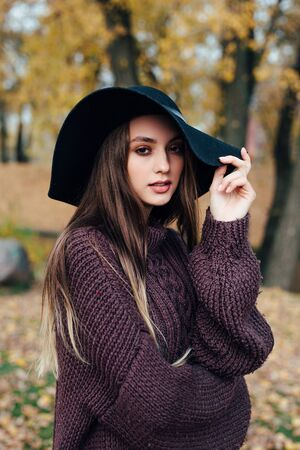 Outdoor fashion photo of young beautiful woman in black hat in autumn park