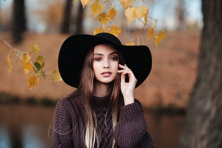 Outdoor atmospheric lifestyle photo of young beautiful lady in black hat