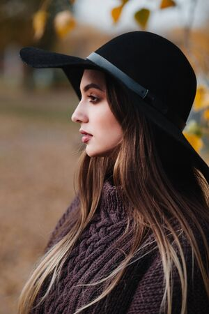 Close-up portrait of stylish girl in elegant black hat in autumn park