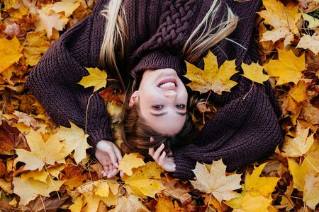 Top view of beautiful young woman lies on autumn leaves and looking at camera.