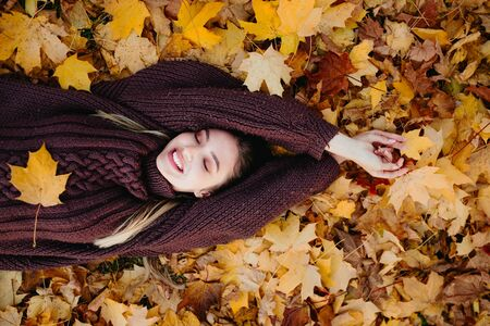 Young woman lying on autumn leaves and enjoying the nature