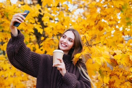 Happy girl in brown sweater is doing selfie using a smartphone and smiling in the autumn park