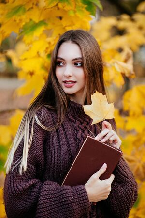 Portrait of beautiful girl with book in the autumn park