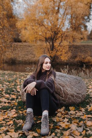 Young stylish girl sitting outdoor in autumn scenery