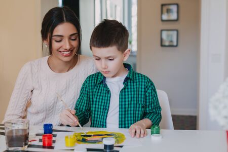 Mother and little son together paint at home. Woman helps her child
