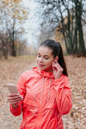 Portrait of a smiling healthy woman with earphones standing in park after running.