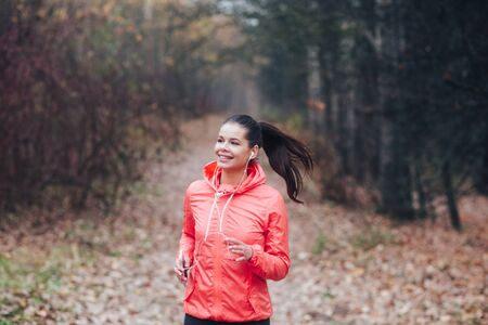 Runner is jogging in overcast day in the autumn park background.