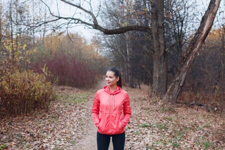 smiling caucasian woman standing in autumn park after running.