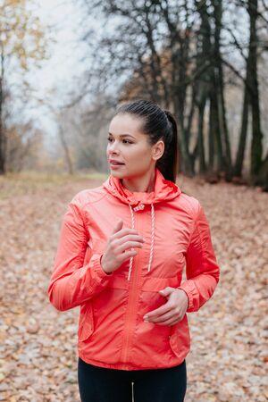 young beautiful caucasian woman jogging workout training in autumn park.