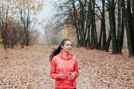 Young woman jogging in beautiful autumn city park in colorful fall foliage