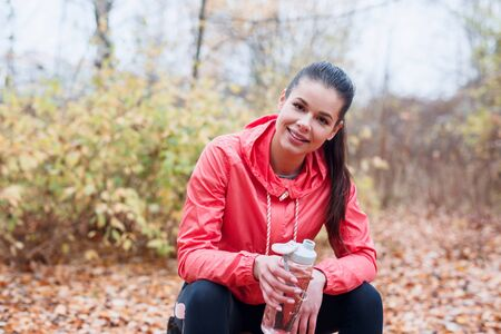 tired runner sitting in the autumn park and drinking water from sport bottle Reklamní fotografie