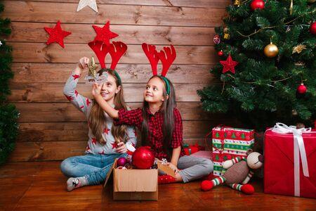 Frohe Weihnachten und schöne Feiertage. Süße kleine Schwestern schmücken den Baum zu Hause.