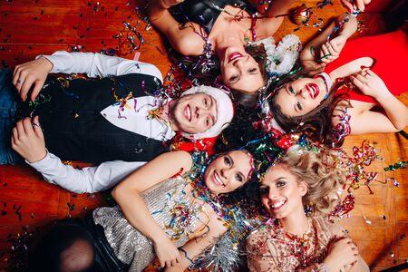 Grupa przyjaciół w klubie bawi się i leży na podłodze. Impreza sylwestrowa