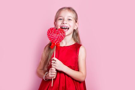 Little happy girl in red dress with a heart-shaped lollipop Stok Fotoğraf