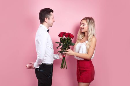 Handsome elegant guy is proposing to his beautiful girlfriend, giving her roses and smiling