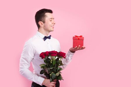 Young handsome man with beautiful flower bouquet and red gift box on pink background