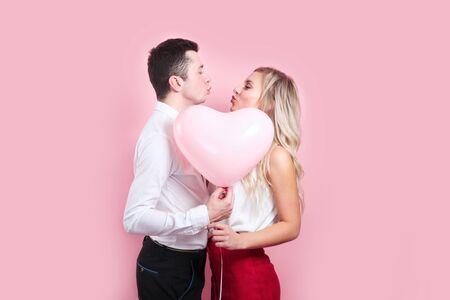 Paar bedeckt Gesichter mit Ballon auf rosa Hintergrund