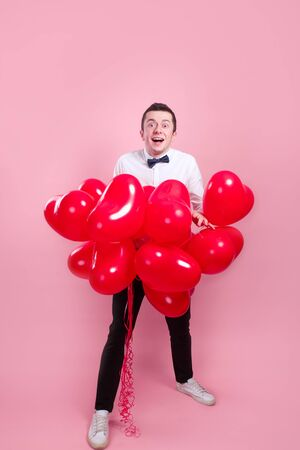 Elegant young man with heart shape air balloons on pink background. Valentines Day.