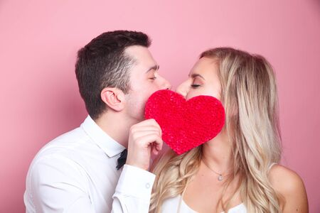 Young couple holding red love heart and kissing. Couple in love
