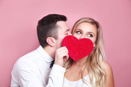 Young couple holding red love heart over eyes and kissing Foto de archivo - 138300066