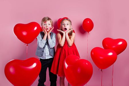 Surprised little boy with red kisses on the skin and girl in red balloons on pink background
