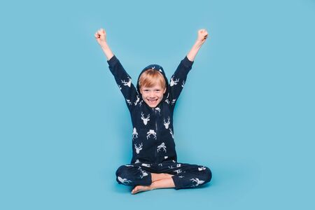 Happy little boy in warm pajamas waking up in the morning