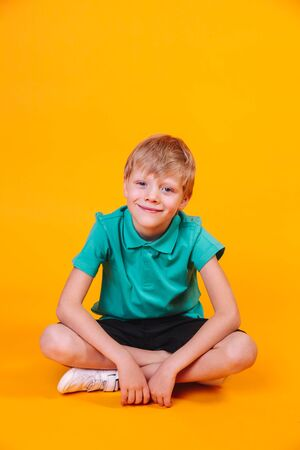 Full length portrait of cute little boy in stylish clothes sitting on yellow background
