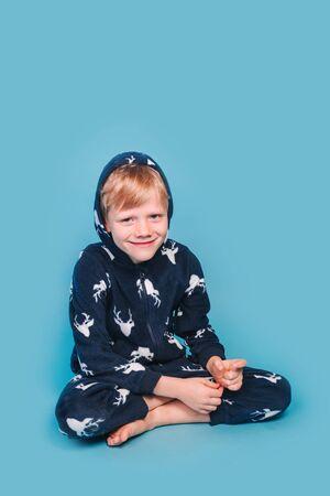 Little boy in blue pyjamas sitting on yellow background