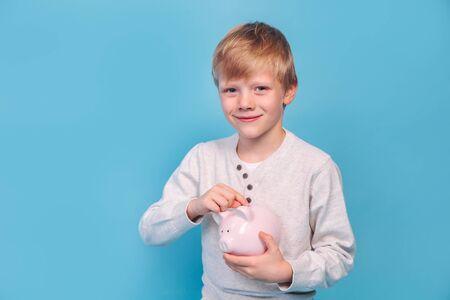 Little boy saving money in a piggybank on blue background