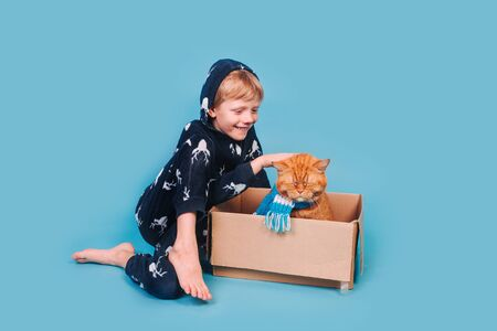Kid in soft warm pajamas playing with red cat 免版税图像
