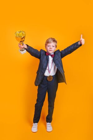 Little boy with trophy in his hands and golden medal