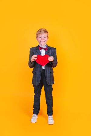 Happy smiling handsome boy with a red heart on yellow background. Valentines Day