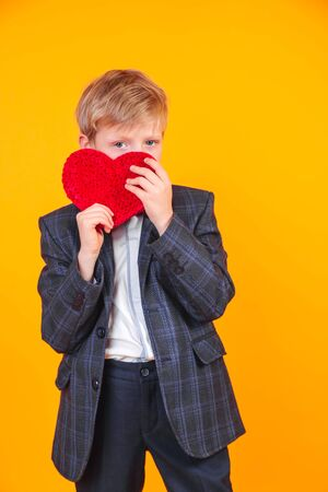 Little blond boy holding heart and laughing at camera on yellow background.