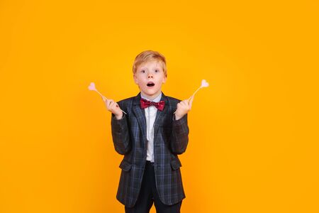 Surprised little boy with pink hearts on yellow background. Valentines Day celebration